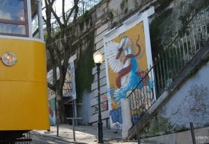 Portuguese street art in Lisbon next to yellow tram