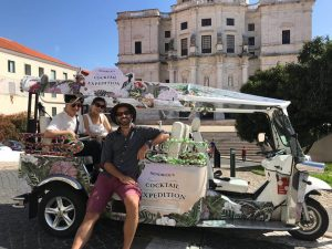 Guide and clients on a tuk tuk in Lisbon