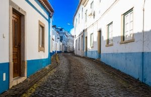 narrow street with white and blue houses in Ericeira Portugal