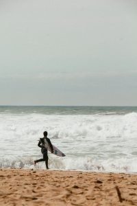 man going to surf in Portugal