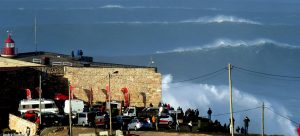 group of people looking at giant waves in Nazare Portugal