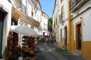 narrow street with typical white and yellow houses in Evora Portugal