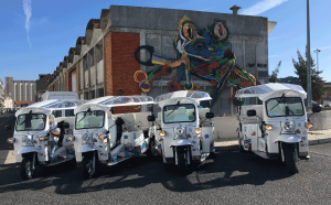 fleet of tuk tuk near street art in Lisbon